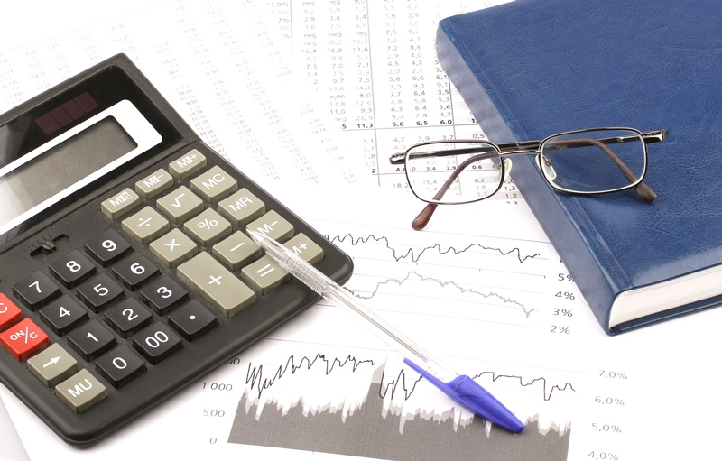 Business still-life of a pen, charts, glasses, diary, calculator